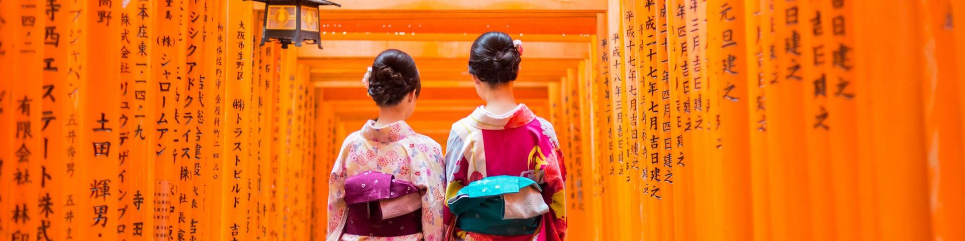 Two geisha stand in front of a red wooden tori gate at fushimi inari shrine in Kyoto, Japan